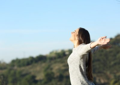 Happy woman stretching arms breathing fresh air